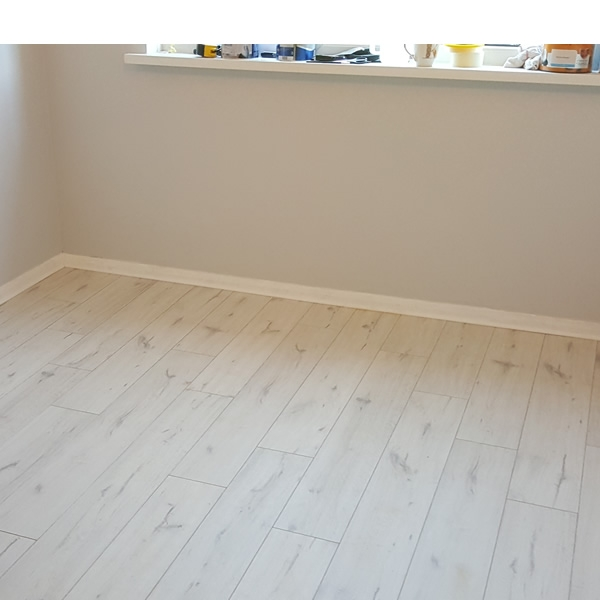 Clean cut bedroom laminate flooring - white skirting boards and scotia beading